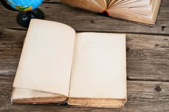 Open old book with blank pages on wooden table with globe close Stock Image