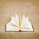 Open old book on brown canvas background Royalty Free Stock Images