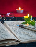An open old book by the candlelight Royalty Free Stock Photography