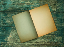 Open old book on grungy wooden background. Paper texture Stock Photography
