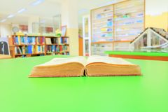 Open old book interior library school on table green blur bookshelves background. Education learning concept with copy space add text royalty free stock photos