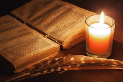 Open old book in the light of a candle Royalty Free Stock Photo