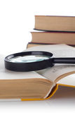 Open old book with loupe on white background. Royalty Free Stock Photography