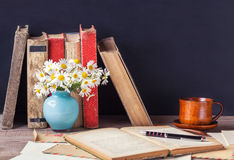 Open old book lying on the wooden table among vintage envelopes. Rustic still life. Royalty Free Stock Photos