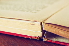 Open old book over wooden table. macro image with selective focuse. filterted image Royalty Free Stock Images