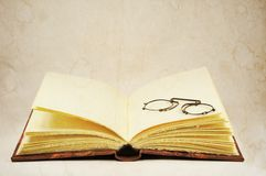 Open old book and pince-nez eyeglasses Stock Images