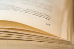 Open old book. Yellowed pages. Page number 179. Paper texture. Macro.  Stock Photos