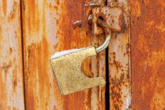 An open old padlock hanging on rusty doors Stock Image