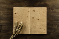 Open old vintage book on the aged wooden background. ears of wheat. Stock Image