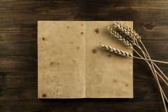 Open old vintage book on the aged wooden background. ears of wheat. Stock Images