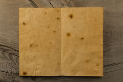 Open old vintage book on the aged wooden background. Two clean sheet of paper Royalty Free Stock Images