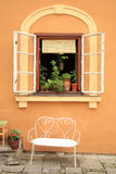 Open old window with bench. Flowers in the open window with bench of the historic house in Old Town in Cesky Krumlov, Czechia, Heritage Unesco Royalty Free Stock Images