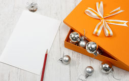 Open orange gift box with silver christmas baubles Royalty Free Stock Images