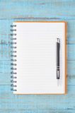 Open orange Notebook and pen on blue wood table for work Stock Images