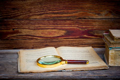 Open oud boek met een vergrootglas Stock Foto's