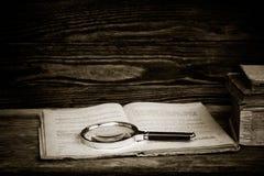 Open oud boek met een vergrootglas en een stapel boeken Royalty-vrije Stock Afbeelding