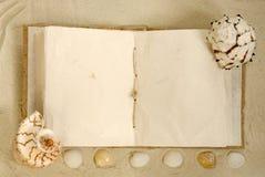 Open oud boek met zeeschelpen op het zand Royalty-vrije Stock Afbeelding