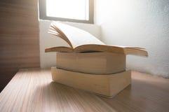 Open oude boeken op een houten lijst met vensterlicht Stock Afbeelding