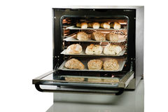 Open oven with fresh baked bread on white background. Royalty Free Stock Image