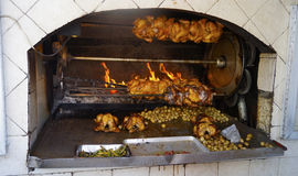 Open oven with some chikens and potatoes in it. A big stone oven being used to bake several chikens an some potatoes and spicy chilly in it Royalty Free Stock Photos