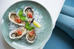 Open oyster stuffed. With papper and lemon on a plate in a cafe table. delicious seafood. top view stock photo