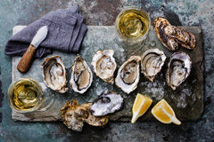 Open Oysters with lemon and wine. Open Oysters Fines de Claire on stone plate with lemon and wine Stock Photo
