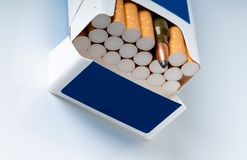 Open pack of cigarettes with a weapon cartridge. Photo concept. Open pack of cigarettes with a filter and a machine-gun cartridge Stock Photos