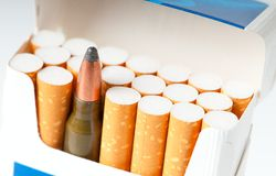 Open pack of cigarettes with a weapon cartridge. Photo concept. Open pack of cigarettes with a filter and a machine-gun cartridge Stock Images