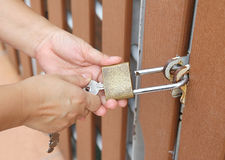 Open padlock. Closeup image of hand use key to open padlock and the brown wooden door Royalty Free Stock Photos