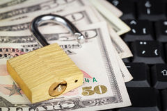 Open padlock and money on a computer keyboard. Open padlock and a stack of money on a black computer keyboard Royalty Free Stock Image