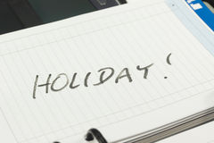 Open page of paper managers diary with an inscription HOLIDAY Stock Photo