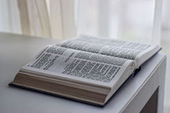 Open pages of the Bible next to the window Royalty Free Stock Image