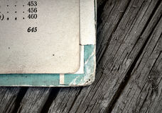Open pages of old shabby books on a background of aged wood Stock Images