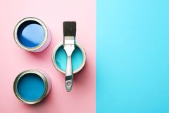 Open paint cans, brush and space for text on color background. Top view royalty free stock photo