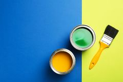 Open paint cans, brush and space for text on color background. Top view stock photography