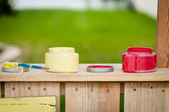Open paint containers on a wooden booth. Two open containers of paint, red and yellow, and a paintbrush sitting on the top of a homemade booth Royalty Free Stock Photos