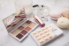 An open palette of shadows of eight warm shades and lipstick in a metallic tube pink gold. Still life in the style of boudoir. royalty free stock photo
