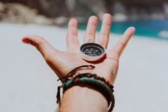Free Open Palm With Stretched Fingers Holding Black Metal Compass Against White Sandy Beach. Find Your Way Or Goal Concept Royalty Free Stock Photo - 122681475