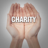 Open palms with word charity Stock Photography