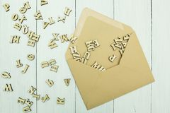 Open paper mail envelope with scattered wooden letters inside on a white table stock images