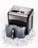 Open paper shredder. An open paper shredder with shredded paper all around