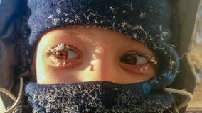 Close-up of frost on the eyelashes of a boy on the street in winter royalty free stock photos
