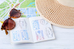 An open passport with sunglasses, map and a hat. Stock Image