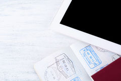 Open passports with visa stamps and tablet. Royalty Free Stock Image