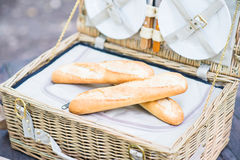 Open picnic basket with bread inside over a wooden table in the park. Royalty Free Stock Photos