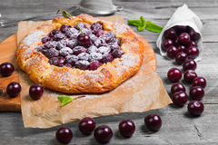 Open pie tart dough with ripe cherries. Open pie tart dough sprinkled powdered sugar with ripe cherries on paper on board, fresh cherry in white paper bags, red Stock Image