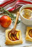 Open pies of puff pastry with peach (nectarine), thyme and honey. Breakfast Stock Photos