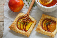 Open pies of puff pastry with peach (nectarine), thyme and honey. Breakfast Royalty Free Stock Photos