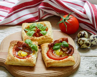Open pies of puff pastry with quail egg, tomatoes, bacon and Basil. Breakfast Royalty Free Stock Photo