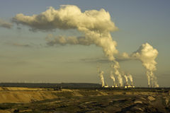 Open-pit lignite mining in sun. Open-pit mining for lignite (brown coal) that is burnt and transformed to electricity by the power stations at the horizon stock photography